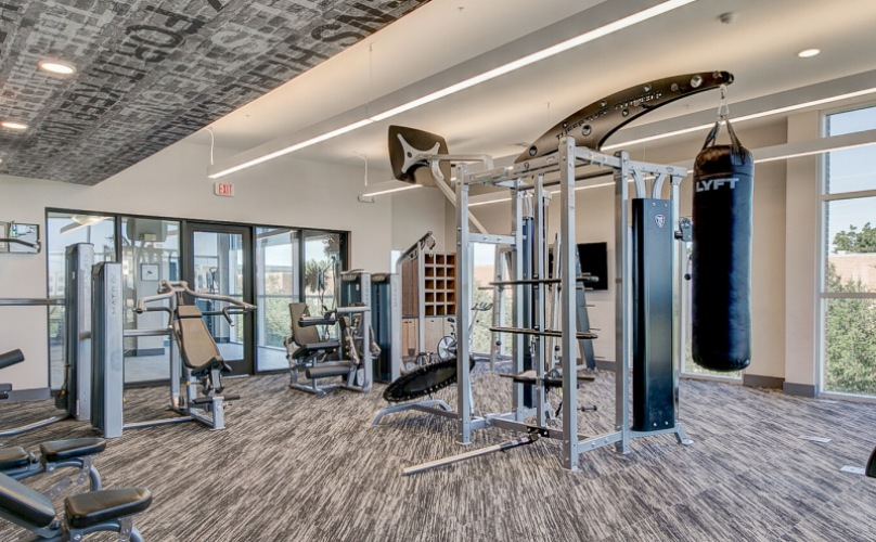 Wycliff Apartments in Dallas fitness center with assorted weight equipment